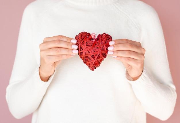 Handen die het vooraanzicht van de hartdecoratie houden
