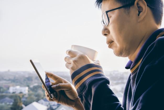 Handen die hete kop van koffie of thee en telefoon mobiel in ochtendzonlicht houden