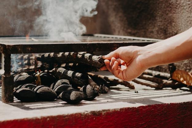 Handen die hout en houtskool aansteken voor een grill.