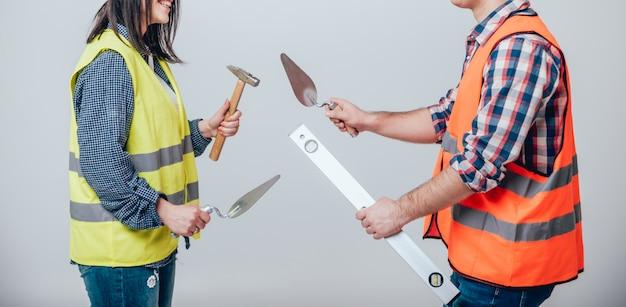 Handen die hulpmiddelen voor huisvernieuwing houden