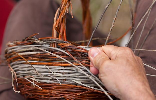 Handen die in een mand costruction werken