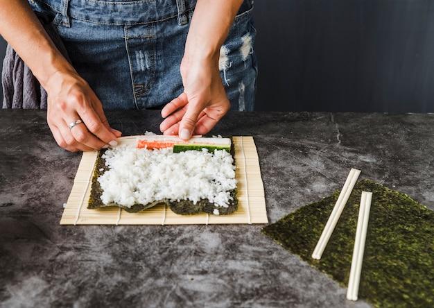 Handen die ingrediënten plaatsen op rijst