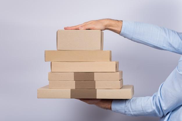 Handen die kartondozen op witte ruimte houden. bezorg pakketten