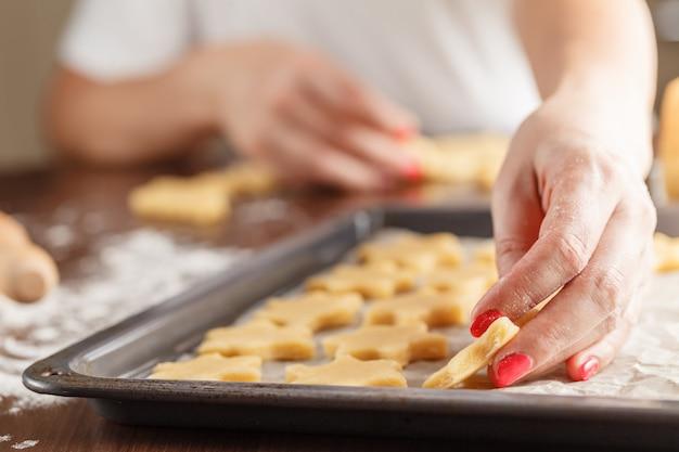 Handen die kerstmiskoekjes met metaalsnijder maken
