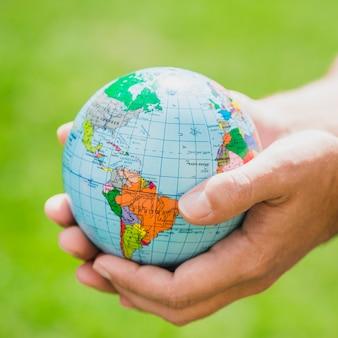 Handen die kleine bol houden tegen groene achtergrond