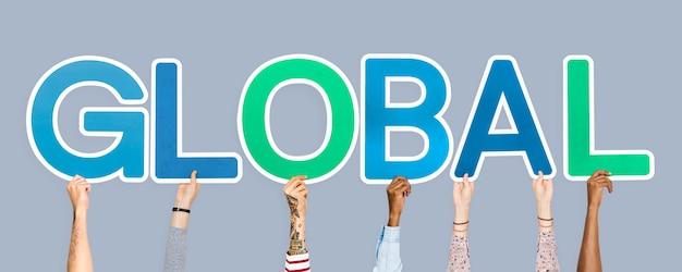 Handen die kleurrijke brieven steunen die het globale woord vormen