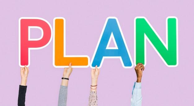 Handen die kleurrijke brieven steunen die het woordplan vormen
