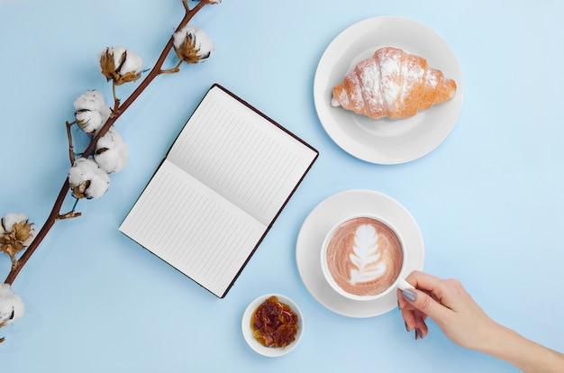 Handen die koffie en notitieboekje met croissant en katoenen tak houden