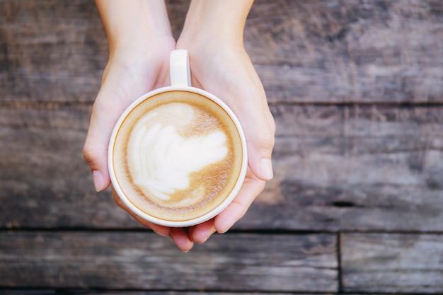 Handen die koffiecop op hout houden.