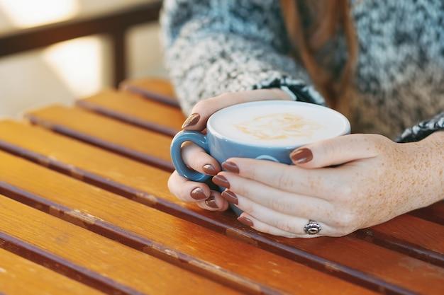 Handen die kop met hete witte latte houden