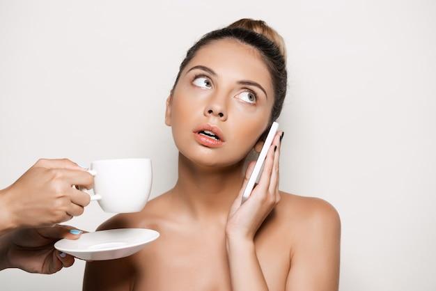 Handen die kop van koffie aanbieden aan vrouw die op telefoon spreekt
