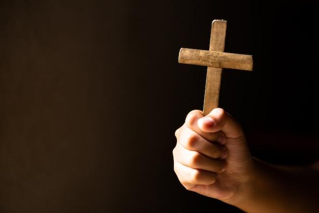 Handen die kruis houden tijdens het bidden.