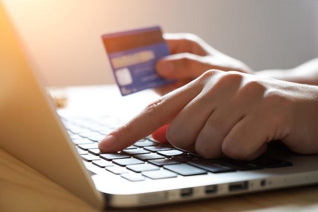 Handen die laptop computer voor online thuis het winkelen met behulp van