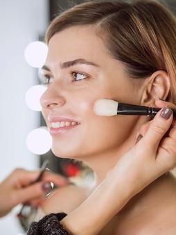 Handen die make-up op gelukkig model toepassen