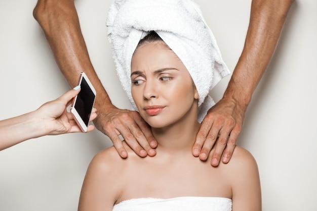 Handen die massage doen en telefoon geven aan jonge mooie vrouw