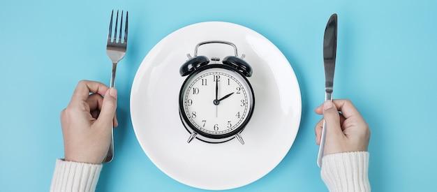 Handen die mes en vork boven wekker op witte plaat houden