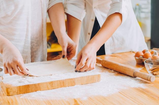 Handen die met deeg werken die koekjes voorbereiden