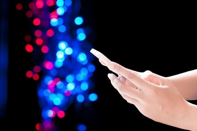 Handen die mobiele telefoon op kerst achtergrond houden. feestelijke elegante achtergrond met bokeh lichten en sterren, kopieer ruimte