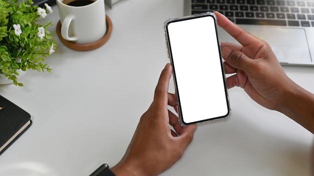 Handen die modelsmartphone op bureau gebruiken.