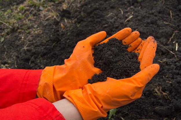 Handen, die oranje rubberhandschoenen met de grondachtergrond draagt