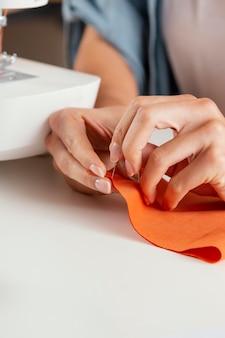 Handen die oranje stoffenclose-up naaien
