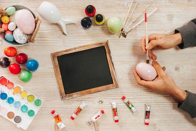 Handen die paasei in workshop schilderen