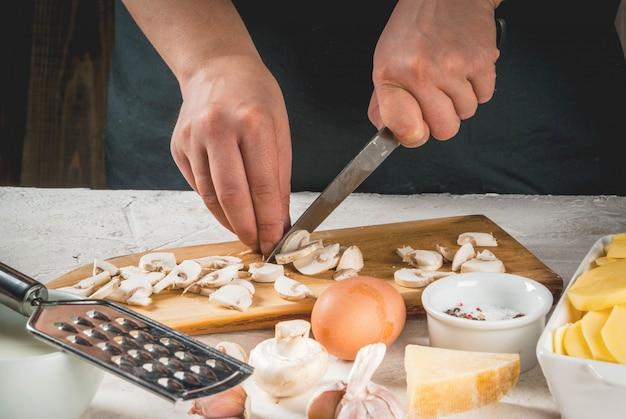Handen die paddestoel snijden die door ingrediënten wordt omringd