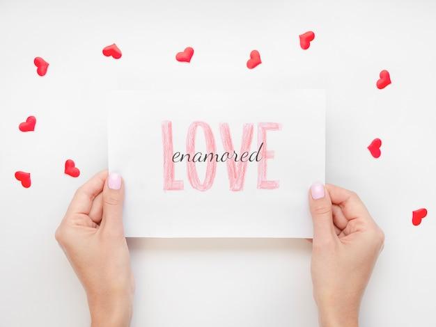 Handen die papier houden dat door harten wordt omringd