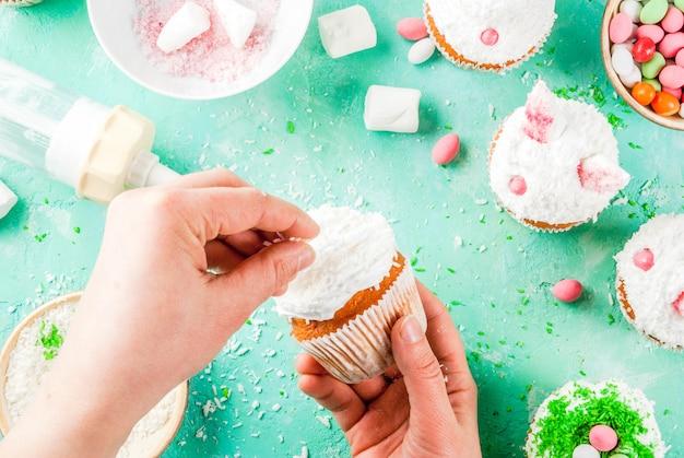 Handen die pasen cupcakes met konijntjesoren maken
