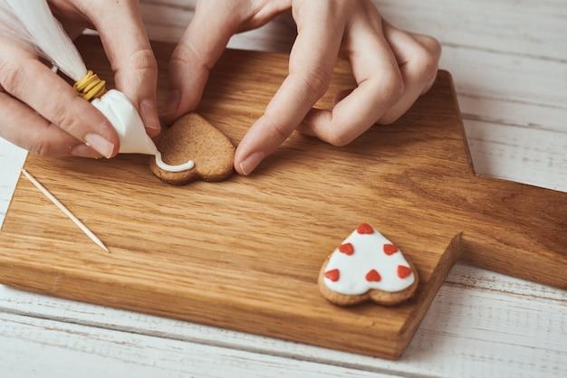 Handen die peperkoekkoekjes met suikerglazuur verfraaien