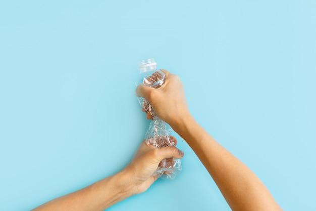 Handen die plastic flessen verpletteren. plastic gebruik concept. aantrekkelijke ecologische probleem positieve poster.
