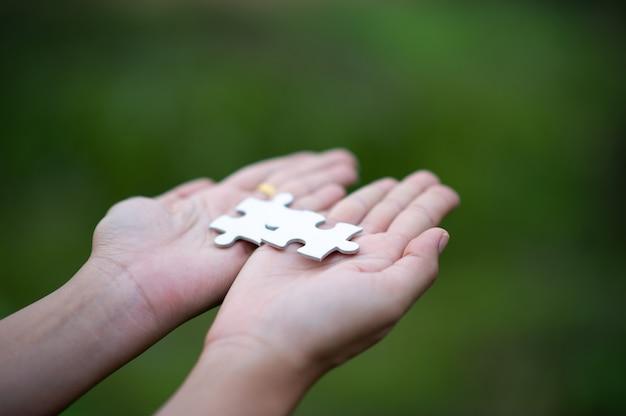 Handen die puzzelstukjes houden