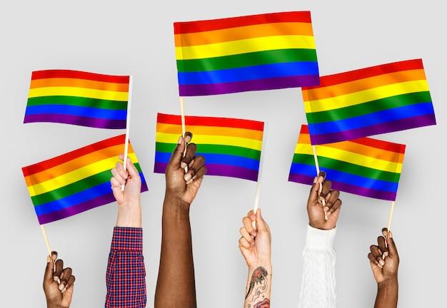 Handen die regenboogvlaggen golven