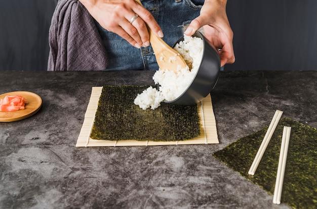Handen die rijst op geroosterd zeewier zetten