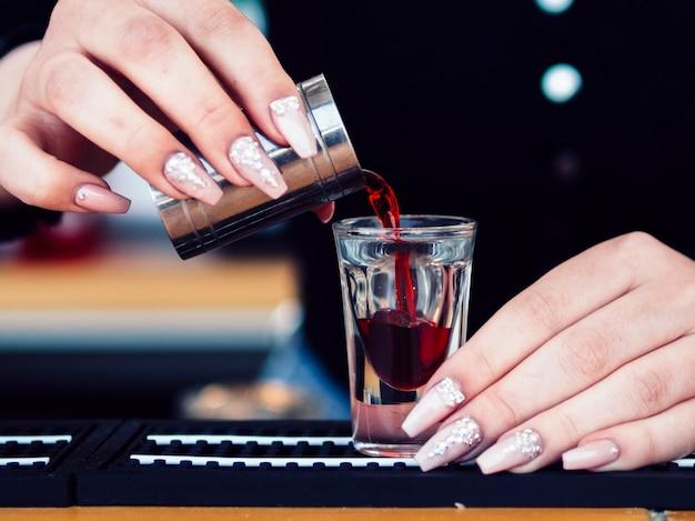 Handen die rode alcoholische drank in glas gieten
