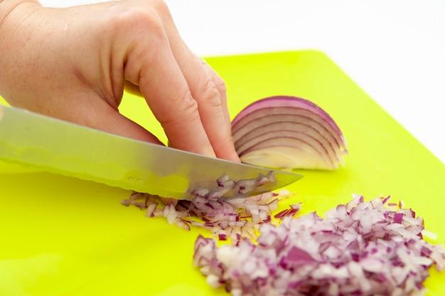 Handen die rode ui snijden om traditionele braziliaanse vinaigrette te bereiden