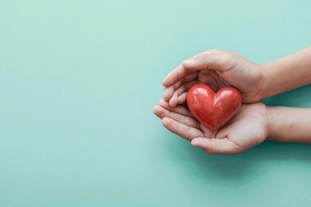 Handen die rood hart op blauwe achtergrond houden