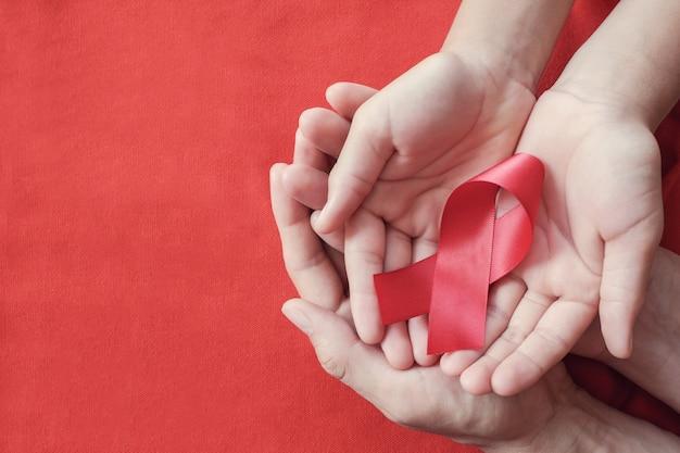 Handen die rood lint op rode achtergrond houden, hiv voorlichtingsconcept