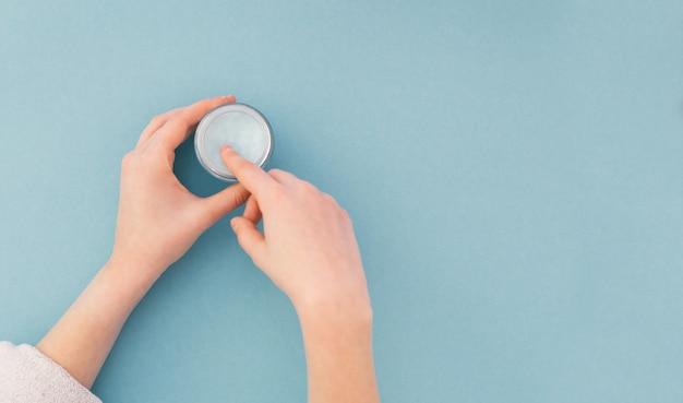 Handen die roombuis houden, vrouwenhanden met natuurlijke manicurespijkers die kosmetische handroom op blauw toepassen