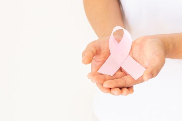 Handen die roze lintkrul op witte geïsoleerde stof met exemplaarruimte houden