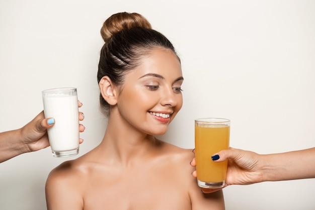 Handen die sap of melk aanbieden aan jonge mooie vrouw