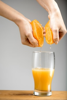 Handen die sap van sinaasappel in glas drukken