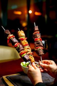Handen die shish kebab met kleurrijke groene paprika's houden