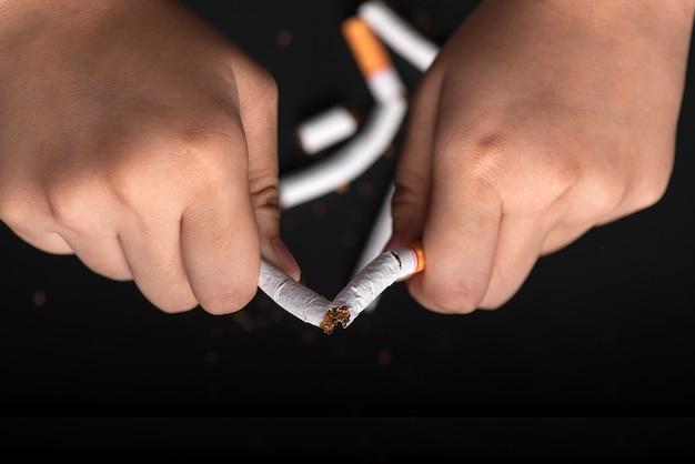 Handen die sigaret breken voor stoppen met roken