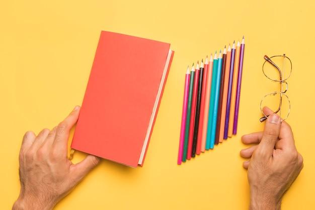 Handen die sketchbook dichtbij met potloden houden