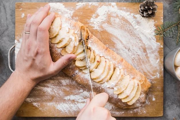 Handen die smakelijke cake op hakbord snijden