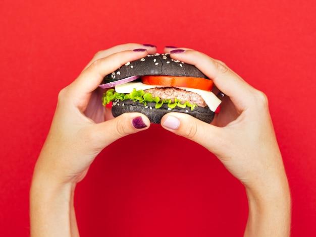 Handen die smakelijke hamburger met rode achtergrond houden