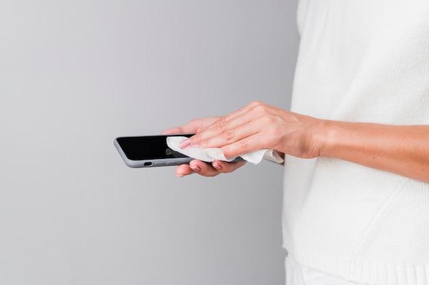 Handen die smartphone desinfecteren
