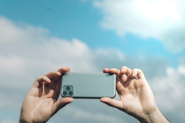 Handen die smartphone met bewolkte hemel houden