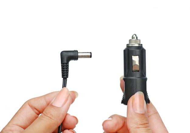 Handen die stopcontactdoos in auto 12 volt houden aan het laden voor enz. geïsoleerd op witte achtergrond